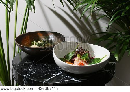Salmon Steak Salad And Dim Sum In Plate On Marble Table And Tropic Plants On Back