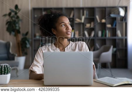 Dreamy African American Woman Looking To Aside, Distracted From Laptop