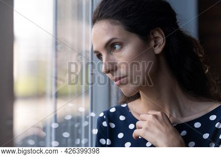 Sad Thoughtful Hispanic Woman Looking Out Window In Deep Thought