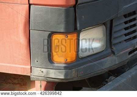One Front Large Glass Headlight On The Cab Of A Red Black Truck On The Street