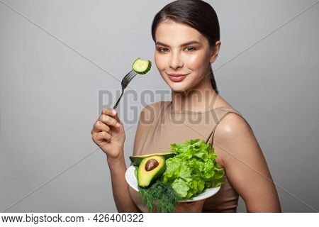Young Model Healthy Woman Eating Green Vegetables Avocado, Cucumber And Green Herbs. Detoxification,
