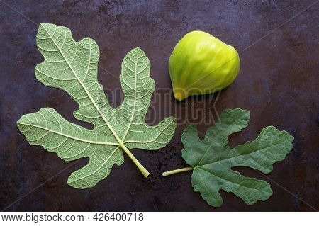 Ripe Fig Fruit And Green Leaves Of Fig Tree On Black Metal Background.  Flat Lay, Copy Space