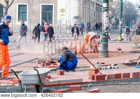 Timisoara, Romania - September 05, 2015: Man Cutting Bricks. Workers And People Walking On The Stree