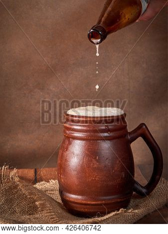 Beer Clay Brown Mug With Beer On A Wooden Table On A Dark Background. A Stream Of Light Beer Pours I