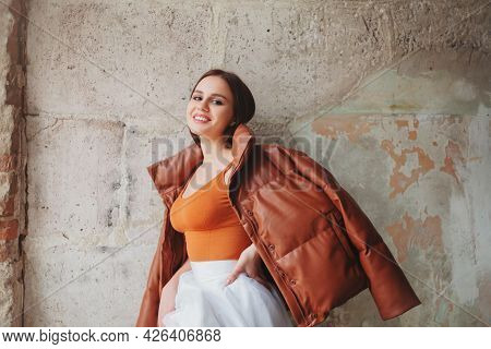 Optimistic Female Model In Trendy Coat Holding Hand On Waist And Looking At Camera With Smile While