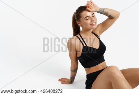 Image Of Female Athlete Sitting On Floor Isolated White Background. Sportswoman Smiling Satisfied, R
