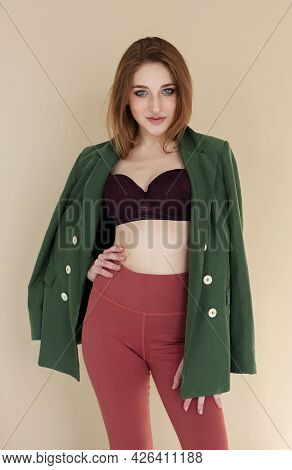 Self Assured Young Woman In Stylish Jacket And Bra Holding Hand On Waist And Looking At Camera Again