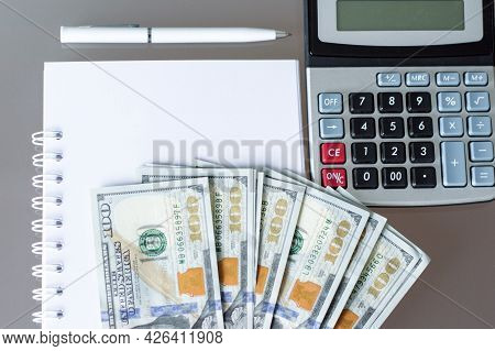 Calculator, Dollars Banknotes, Blank Notebook On A Dark Desktop Next With Calculator And White Pen.