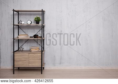 Shelf With Books And Plant - Copy Space Over Concrete Wall Background