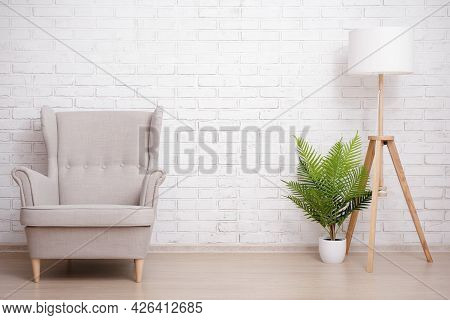 Armchair, Lamp And Plant Over Brick Wall Background With Copy Space