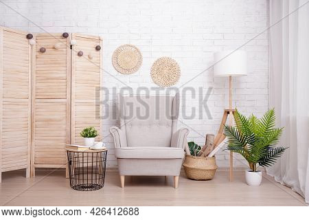 Interior Of Room With Armchair, Lamp And Plants Over Brick Wall Background