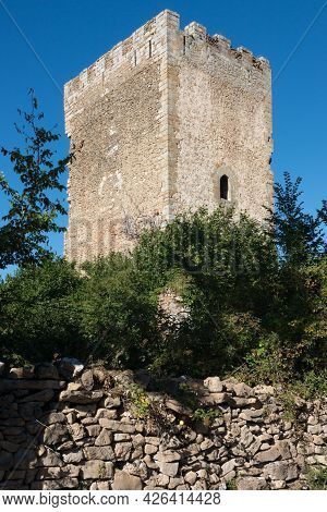 Ancient Stone Tower With A Small Window. Blue Sky, No People, Trees Around And Surrounding Wall. Mer