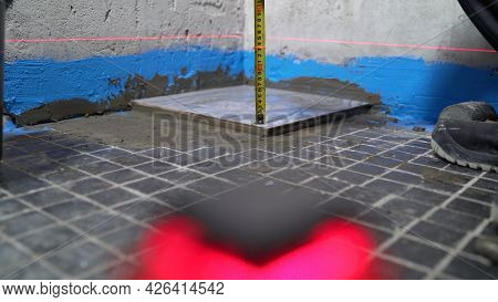 Checking The Tiles In The Bathroom. Quality Control When Laying Ceramic Tiles On The Floor. The Tech