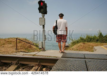 Crossing The Railway Tracks Across The Railway Tracks In The Daytime. Safety Concept For Road Users.
