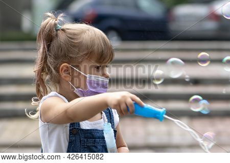 A Little Girl Of 3-4 Years Old With Blonde Hair Blows Soap Bubbles On The Street. Children's Enterta