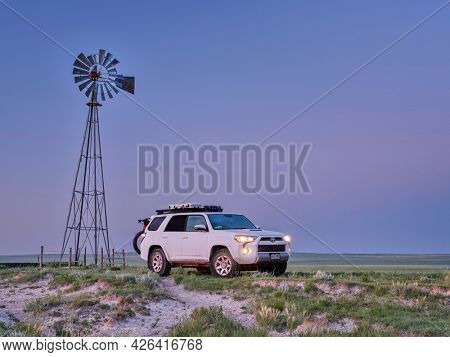 Grover, CO, USA - July 7, 2021: Toyota 4Runner SUV (2016 Trail edition) before sunrise in Pawnee National Grassland in northern Colorado, summer scenery with a windmill and cattle water tank.