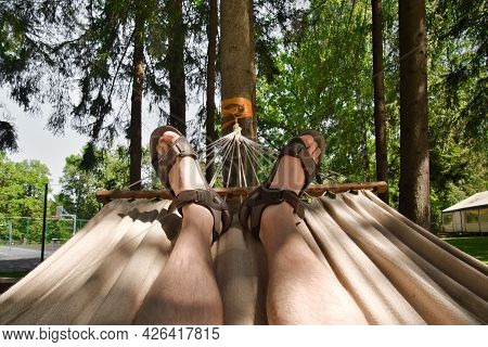 Male Feet In Sandals On Hammock. Man Resting On Hammock At Summer Day In Park.