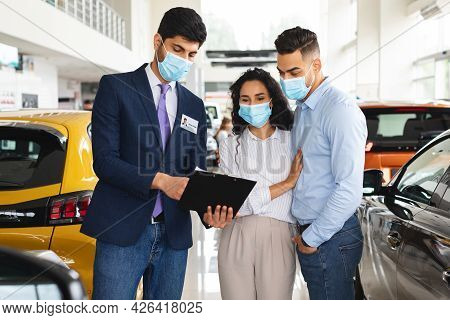 Arab Couple In Face Masks Visiting Automobile Showroom Or Exhibition