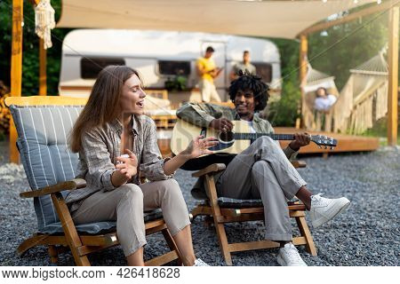 Black Guy Playing Guitar, His Female Friend Singing, Sitting In Lounge Chairs Near Motorhome, Having
