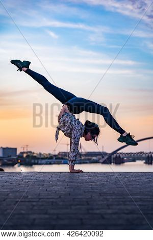 Silhouette Of Flexible Female Circus Artist Doing Handstand On The Dramatic Sunset And Cityscape. Co