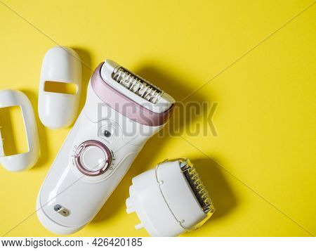 Female Electric Epilator In White On A Yellow Background. There Are Additional Attachments Nearby. T