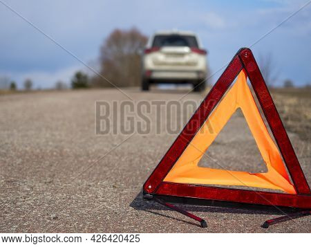 Red Emergency Stop Sign. In The Background, The Car Has Stopped And The Emergency Lights Are Flashin