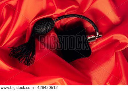 Black Bottle Of Eau De Toilette Or Perfume With Long Tassel Spray Pomp Lies On Red Background Of Flo