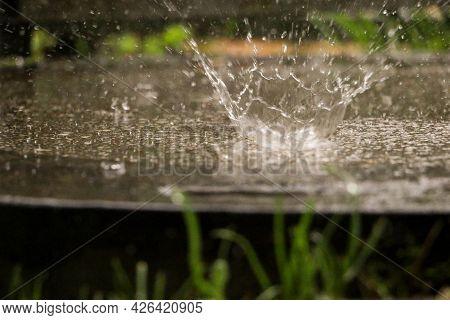 Heavy Rain Falls On A Manhole Cover