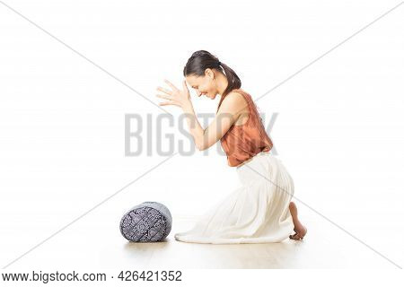 Restorative Yoga With A Bolster. Young Sporty Attractive Woman In Bright White Yoga Studio, Lying On