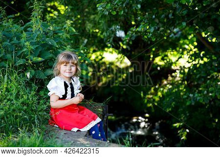 Little Preschool Girl In Red Riding Hood Dress Sitting In Forest By A Brook. Cute Toddler Child Enjo