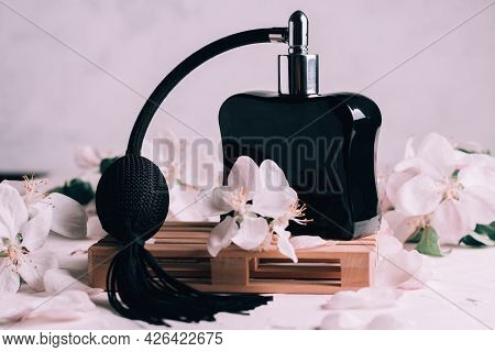 Black Bottle Eau De Toilette Or Perfume With Long Tassel Spray Pomp, On Wooden Podium In Form Of Pal