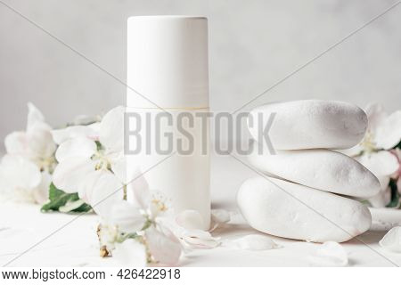 Antiperspirant Roll-on Deodorant Near Stack Of White Pebble Stones On Light Plaster Surface With App