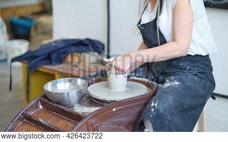 Female Potter Creating A Earthen Jar On A Potters Wheel