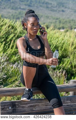 Concerned Afro American Woman Talking On Her Phone On A Break After Exercising