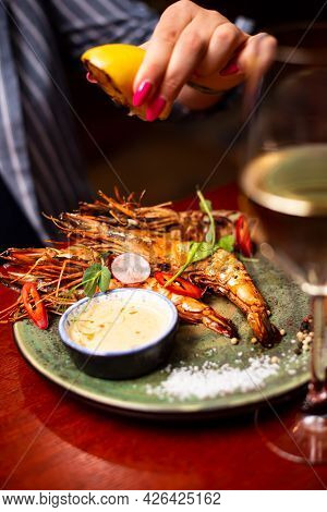 Delicious Langoustine Shrimps In Restaurant On A Wooden Table. Tasty Seafood With Wine In Cafe Menu.