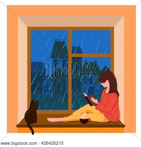 A Girl Sits At The Window, Reads A Book And Drinks Tea While It Is Raining Outside The Window. The C