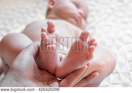 Mother Holding Baby Feet In Hands. Legs Newborn In Female Parents Hand. Small Children's Feet In The