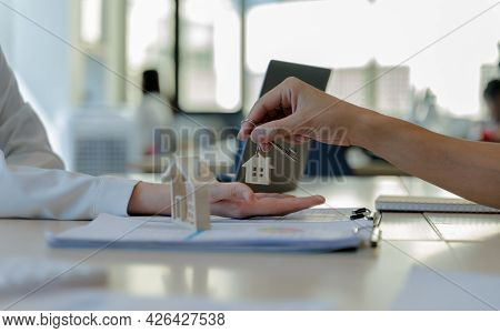 Real Estate Agents Giving House Keys To Customers After Signing Contract. The Concept For Purchasing