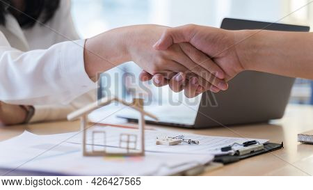 Woman Real Estate Agents Or House Seller And Customers Shake Hand, After Discussing About Buying A H