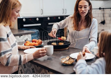 Young Woman Fries Curds Cakes Or Syrniki And Treats Her Guests