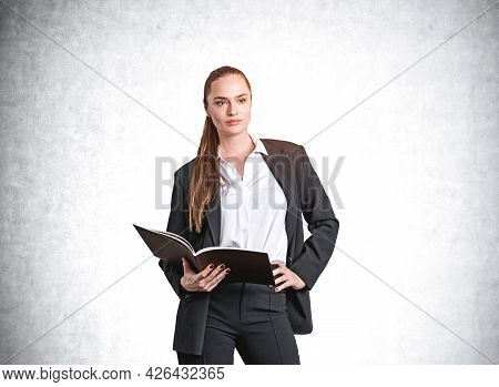 Confident Attractive Businesswoman In Formal Suit And Shirt Is Holding A Notepad, Holding Hand On Wa