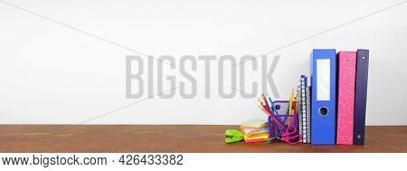 School Binders And Supplies On A Wood Shelf Against A White Wall Banner Background. Back To School C