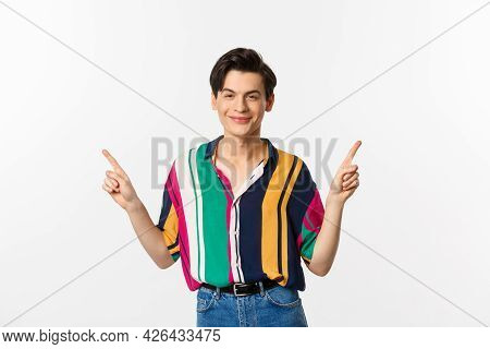 Handsome Queer Man Pointing Fingers Sideways, Smiling Pleased And Showing Two Choices, Standing Over