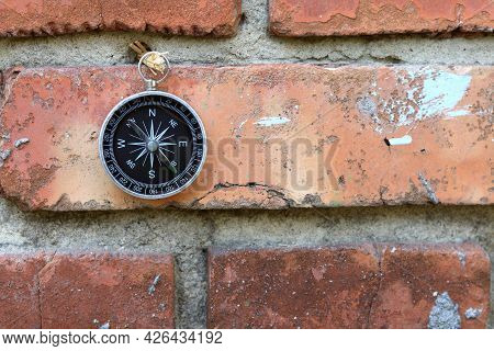 Classic Navigation Compass On Brick Wall Background As Symbol Of Tourism With Compass, Travel With C