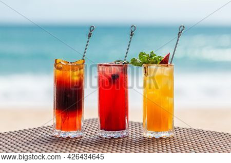 Set Of Three Refreshing Fruit Cocktails Standing On Table On Beach, Blurred Turquoise Sea On Backgro