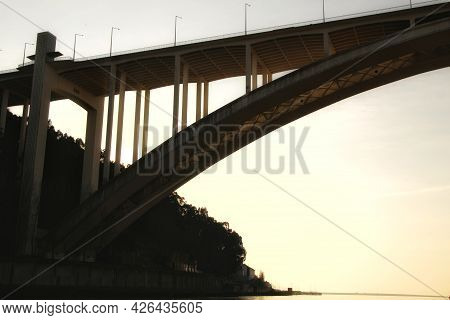Beautiful And Colossal Arrabida Bridge Over The Waters Of The Douro River In Porto At Sunset