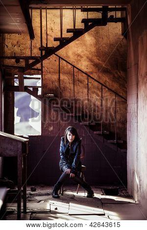 Young beautiful woman inside rusty building.