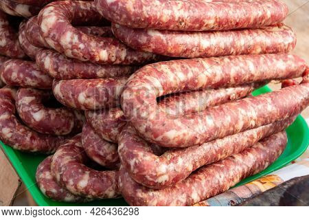Home-made Dried Sausage At The Farm Market. Close-up. Dried And Smoked Sausages At The Farmers' Mark