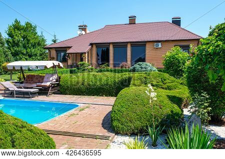 European Style Villa With Pool And Garden With Nicely Trimmed Bushes And Stones In Front Of The Hous