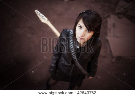 Young beautiful female performer posing with her electric guitar.